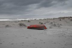 Море, пляж и травы в зиме, красная шлюпка Стоковые Фотографии RF