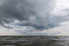 Море развевает на песчаном пляже с бурным небом Стоковые Изображения