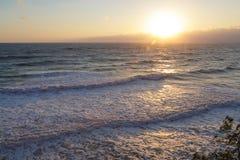 Море развевает против заходящего солнца Стоковая Фотография