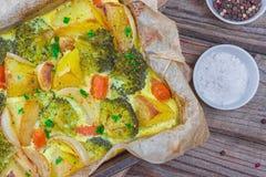 Моркови брокколи, картошки, белый лук и чеснок с сотейником яйца чеддера в печь блюде на деревянной предпосылке Взгляд сверху, эк стоковые фотографии rf