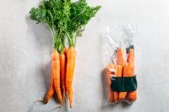 Моркови в полиэтиленовом пакете ПРОТИВ НИКАКОЙ сумки Выберите более менее пластиковое при покупке овощей стоковое изображение rf