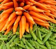 Моркови конца-вверх и стручки гороха Стоковые Фото