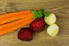 Моркови, свеклы и луки на деревянном countertop Стоковые Изображения