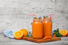 Морковь и апельсиновый сок Бутылки здоровой, органические, smoothie плодоовощ на деревянной предпосылке Коктеиль Vegan скопируйте Стоковое Фото