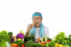 Морковь пожилого человека сдерживая на студии Стоковые Фото