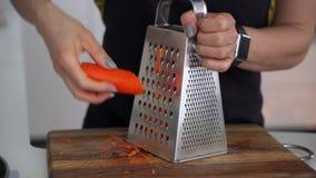 Морковь решеток рук женщины свежая сырцовая оранжевая на большой терке металла для салата лета на обед Источник витаминов и акции видеоматериалы