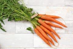 Морковь с ярлыком tha на деревянной предпосылке Стоковая Фотография