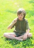 Мороженое мальчика наблюдая Стоковые Фотографии RF