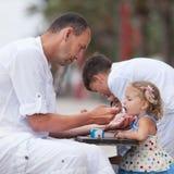 Мороженое дочери младенца отца подавая Стоковая Фотография