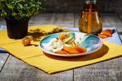 Мороженое с физалисом и высушенными плодоовощами на плите и на ткани Питье около мороженого на деревянной предпосылке Стоковое Изображение RF