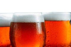 Морозные стекла холодного пива пенятся, предусматриванный с падениями, крупный план Изолировано на белизне Стоковое Изображение RF