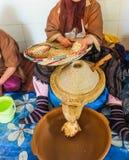 Морокканская женщина показывает стержени argan и положила их в точильщика, Марокко стоковое фото rf