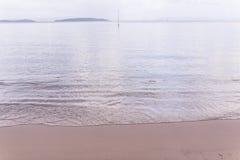 Морская вода на пляже когда малая вода после предпосылки захода солнца Стоковое Изображение RF