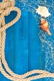 Морские веревочка и раковины сети на голубых дисках Стоковая Фотография