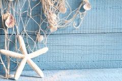 Морские звёзды и рыболовная сеть на голубых досках Стоковое Фото