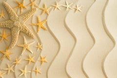 Морские звёзды на золотом песке пляжа с волнистыми линиями Стоковое фото RF