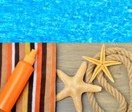 Морские звёзды, полотенце цвета и солнцезащитный крем распыляют против Стоковые Фото