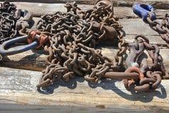 Морские цепи и закрепляют заржаветый и выдержанный текстурированный металл отдыхая на детали дока взморья стоковая фотография