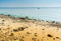 Морское побережье песочно и на горизонте силуэт рыболова и шлюпки Горизонтальная рамка Seascape стоковая фотография rf