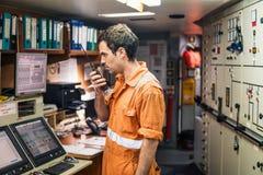 Морской инженер работая на радиосвязи на комнате контроля двигателя Стоковое фото RF