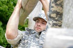 Морской пехотинец, солдат в его армии fatigues выполняет физическую подготовку дальше на курсе obsticle стоковая фотография rf