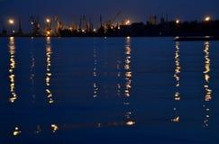 Морской порт в вечере с отражением света от фонариков на воде стоковое фото