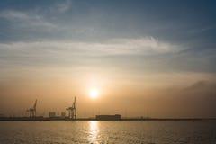 Морской порт с краном и восходом солнца или заходом солнца Стоковые Изображения RF