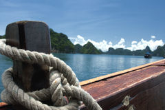 Морской узел связанный из толстой веревки. Sea site of a thick rope tied to a wooden stern Royalty Free Stock Photo