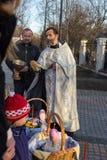 МОСКВА - 11-ОЕ АПРЕЛЯ 2015: Правоверный священник брызгает пасхальные яйца a Стоковая Фотография