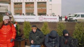 МОСКВА - ОКОЛО АПРЕЛЬ 2018: Люди сидят на стенде с счетом говоря Metrostroi и правительство Москвы акции видеоматериалы
