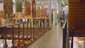 МОСКВА - ОКОЛО ОКТЯБРЬ 2017: Люди идя вокруг дальше лестницы в торговом центре с картинами на выставке видеоматериал