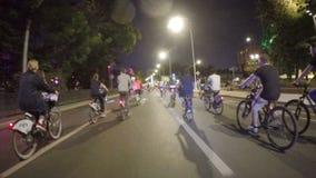 Москва, Россия - 5-ое августа 2018: Много велосипедистов едут в параде ночи через город вечером