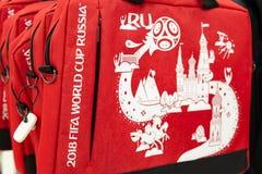 МОСКВА, РОССИЯ - 21-ое апреля 2018: Красная сумка компьтер-книжки в сувенирном магазине с кубком мира ФИФА 2018 mundial символов  Стоковое Фото