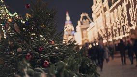 МОСКВА, РОССИЯ - 6-ОЕ ДЕКАБРЯ: Люди идут улицей около входа КАМЕДИ и деревьев украшенных с гирляндой акции видеоматериалы