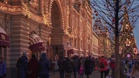 МОСКВА, РОССИЯ - 6-ОЕ ДЕКАБРЯ: Люди идут улицей около входа КАМЕДИ и деревьев украшенных с гирляндой видеоматериал
