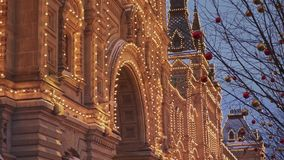 МОСКВА, РОССИЯ - 6-ОЕ ДЕКАБРЯ: Handheld съемка КАМЕДИ украшенная в желтой гирлянде Крыша КАМЕДИ со снегом сток-видео