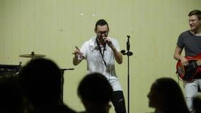 Москва, Россия - 25-ое июля 2018: Привлекательная молодая мужская певица в белой модной футболке поет и танец на этапе с акции видеоматериалы