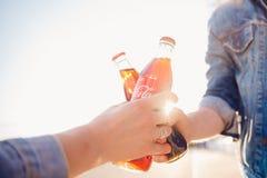 Москва, Россия - 27-ое июня 2019: бутылка стекла в руках, заход солнца кока-колы напитка clink стоковая фотография rf