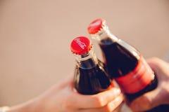 Москва, Россия - 27-ое июня 2019: бутылка стекла в руках, заход солнца кока-колы напитка clink стоковые фотографии rf