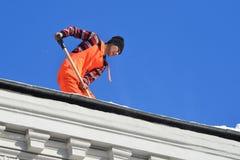 Москва, Россия, 6-ое марта 2018 Работник муниципальной ясности обслуживания крыша от аккумулированного снега в Москве Стоковая Фотография