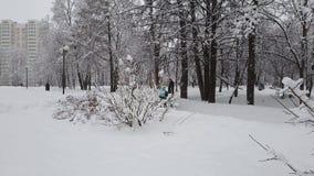 Москва, Россия - 13-ое февраля 2019 Родители с детскими сидячими колясками идут в парк города во время снежности акции видеоматериалы