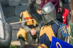 МОСКВА, Росси-июнь 06,2016: Военный поединок 2 средневековых teutonic ратников Бой панцыря рыцарей полностью с шпагами на арене Стоковое Фото