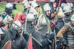 МОСКВА, Росси-июнь 06,2016: Armored ратники в старых костюмах воюя на поле брани Стоковые Фотографии RF