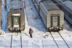 МОСКВА, ФЕВРАЛЬ 01, 2018: Взгляд зимнего дня на железнодорожном работнике обслуживания в оранжевых автомобилях пассажирских поезд Стоковые Изображения