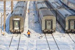 МОСКВА, ФЕВРАЛЬ 01, 2018: Взгляд зимнего дня на железнодорожном работнике обслуживания в оранжевых автомобилях пассажирских поезд Стоковые Фотографии RF