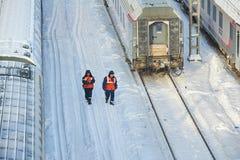 МОСКВА, ФЕВРАЛЬ 01, 2018: Взгляд зимнего дня на железнодорожных работниках обслуживания в оранжевых автомобилях пассажирских поез Стоковая Фотография