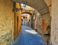 Мостите булыжником каменные руководства улицы вниз с узкого сдобренного переулка стоковое фото rf