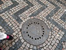 Мостить каменные улицу и крышку люка Стоковая Фотография