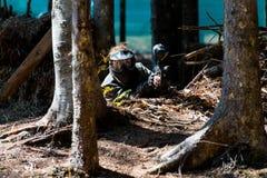Мостовье игрока пейнтбола за деревом Стоковые Изображения RF