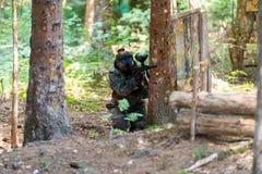 Мостовье игрока пейнтбола за деревом Стоковое Фото